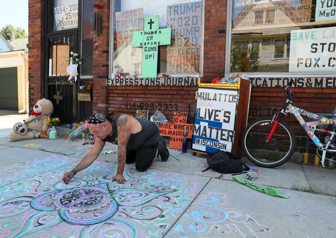 Artist Wisdom Prometheus Grey chalks out a memorial to Bernell Trammell, who was shot and killed outside this building at 915 E. Wright St. in Milwaukee known as eXpressions Journal. Flowers, candles and a teddy bear were also left at the door.