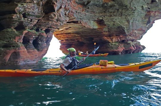 Travis Barningham, owner of Rustic Makwa Den, paddles through sea caves north of Meyers Beach in the Apostle Islands National Lakeshore on July 20, 2020.