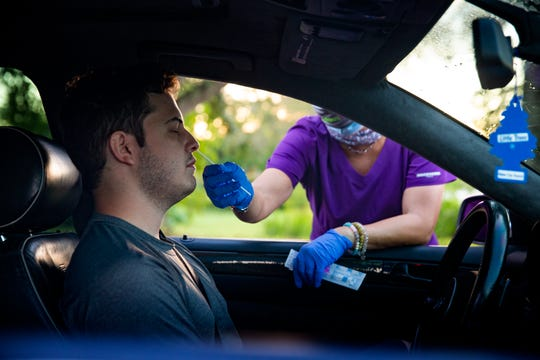 Kristofer Sosa of Naples provides a sample for a COVID-19 test administered by Kat Lucchesi, a CMA with Advance Medical, Friday morning, July 24, 2020, at a parking lot near the Advance Medical Urgent Care Center in Naples