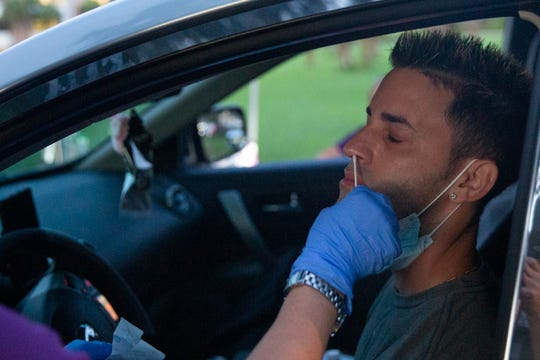 Elvys Ramirez, of Cape Coral provides a sample for a COVID-19 test, Friday morning, July 24, 2020, at a parking lot near the Advance Medical Urgent Care Center in Naples