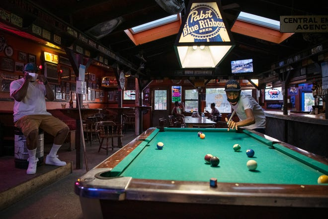 """From left, Troy Foster and Jake Drozek, both of Athens, Ohio, play pool while wearing masks inside the Smiling Skull on West Union Street in Athens, Ohio, on July 20, 2020. """"They've done a great job here,"""" Drozek said while pointing to the bar where signs inform patrons where to order and that drinking at the bar is off limits."""