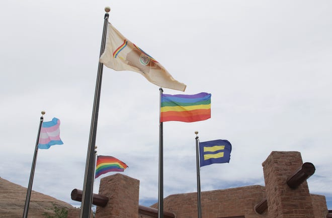 Clockwise from left, the transgender flag, Navajo Nation flag, gay pride flag, equality flag and inclusive flag fly on June 26 in front of the Navajo Nation Council chamber in Window Rock, Arizona.