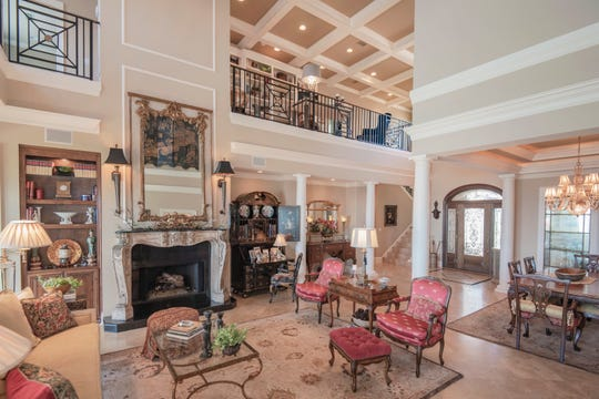 The living area includes a marble fireplace and towering ceilings.