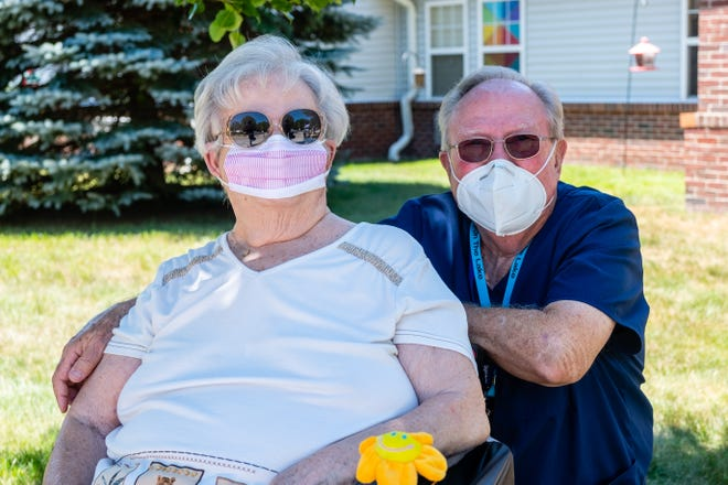 Carol and Larry Burnett hang out on the lawn at Regency-on-the-Lake in Fort Gratiot Friday, July 24, 2020. Larry took a job at the nursing home to be able to see his wife, who is a resident, after the coronavirus pandemic made them stop allowing in-person visits.