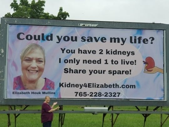 Elizabeth Houk Mullins stands with a billboard that's trying to find a kidney donor for her.