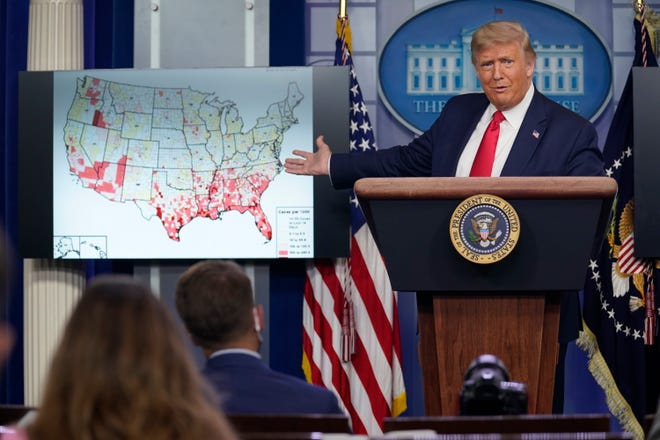 President Donald Trump gestures towards a screen displaying a graphic on the coronavirus outbreak as he speaks during a news conference at the White House, Thursday, July 23, 2020, in Washington.