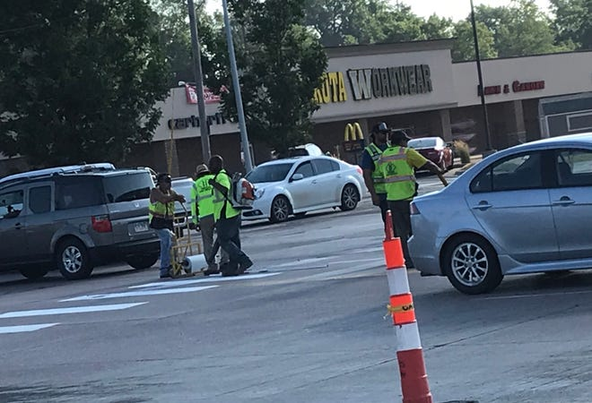 Crews place the finishing touches on lane configuration changes at 41st Street and Minnesota Avenue Friday in Sioux Falls.