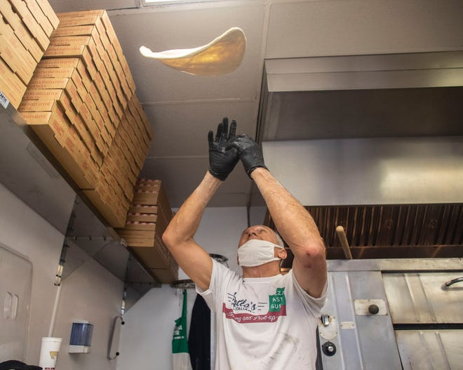 Louis Sollecito, a pizza chef, tosses dough in the air as he prepares a pizza at Solle's Italian for a customer Friday, July 24, 2020.