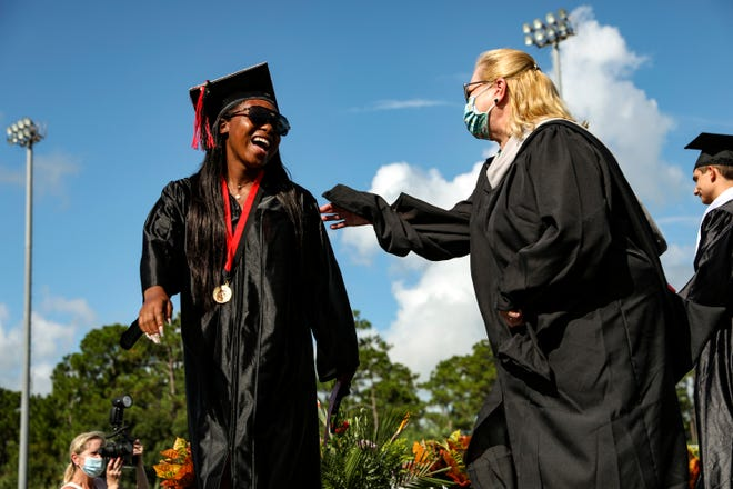Martin County School District Superintendent Laurie Gaylord (right) congratulates South Fork High School graduate Telia Guthrie as she walks across the stage during the school's in-person commencement ceremony on Friday, July 24, 2020, at the school's stadium in Stuart.  Gaylord's successor is to be selected in September.