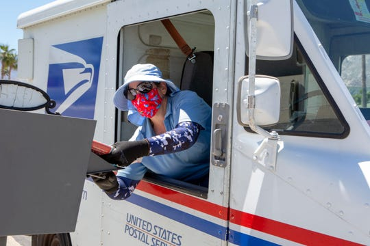 A postal worker delivers mail in Palm Springs during the pandemic. The government agency has been ordered not to have any overtime and to not deliver mail if it doesn't have the staff, an internal memo shows.
