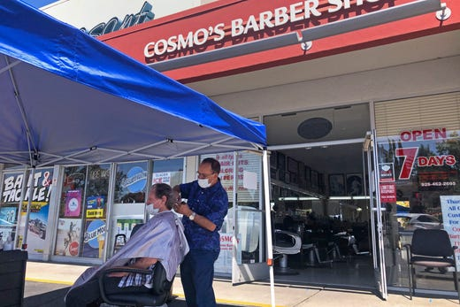 A customer of Cosmo's barber shop receives a haircut in the parking lot in front of the shop on Wednesday, July 22, 2020, in Pleasanton, Calif.  Throughout May and June, California reopened much of its economy, and people resumed shopping in stores and dining in restaurants. But infections began to surge and a new round of business restrictions were imposed, including a ban on indoor dining in restaurants and bars.
