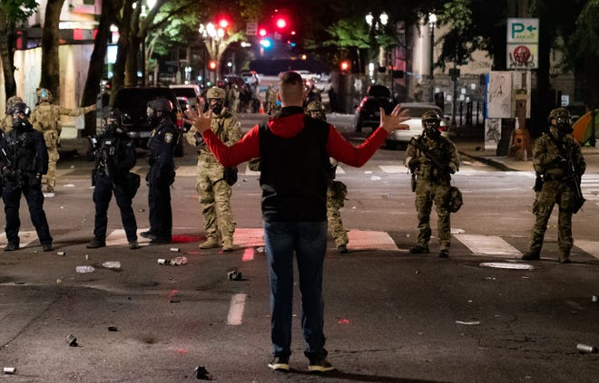 A lone man confronts a line of federal agents during protests near the federal courthouse in Portland, Oregon, in the early hours of July 24, 2020. They fired a teargas canister at his feet moments later.
