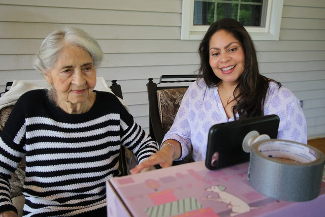 Anna Paulino, 86, and her daughter Laura Rios work on movement exercises with the virtual help of Christine Wentworth, the manager of the adult day care program at EverCare Life. The care is provided remotely via cell phone.