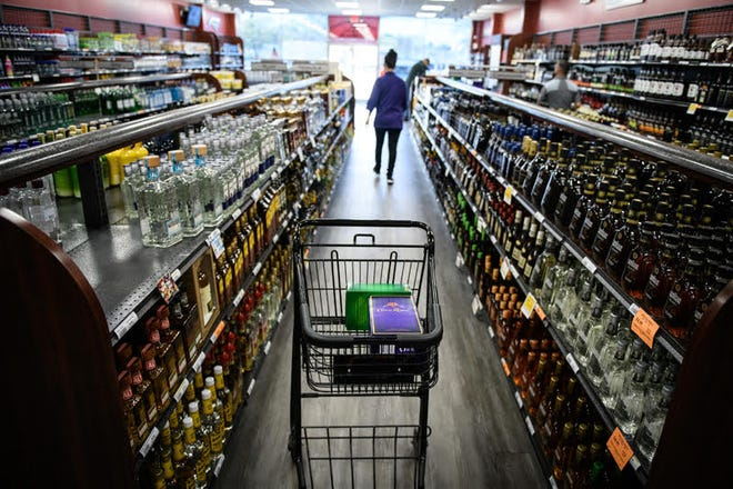 A shopping cart sits in the aisle as the shopper looks down another aisle at the Cumberland County ABC Liquor Store on Owen Drive on Friday, March 27, 2020.  Cumberland County ABC stores are cutting hours and will be limiting total number of customers inside due to Coronavirus.