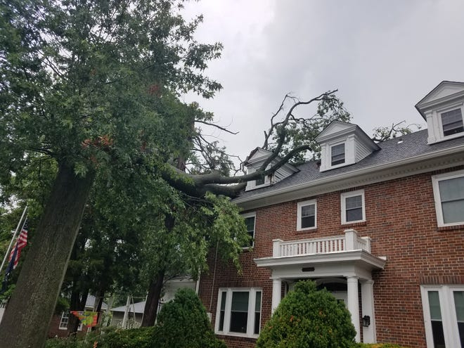 The upper trunk of a towering tree rests on the roof of a Warren Street home in downtown Colonial Beverly following  a powerful  thunderstorm Thursday morning, July 23, 2020. The National Weather Service is investigating to try to determine if the storm was a tornado.