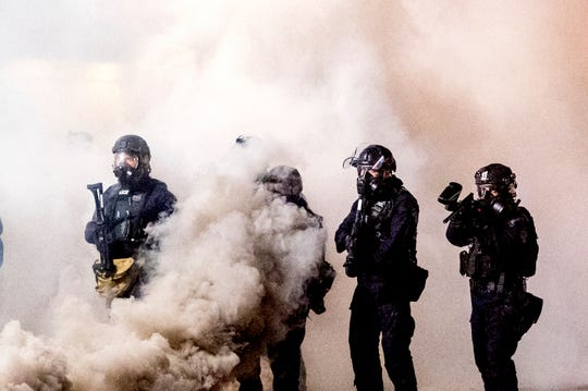 FILE - Int his July 24, 2020, file photo Federal officers use chemical irritants and projectiles to disperse Black Lives Matter protesters near the Mark O.