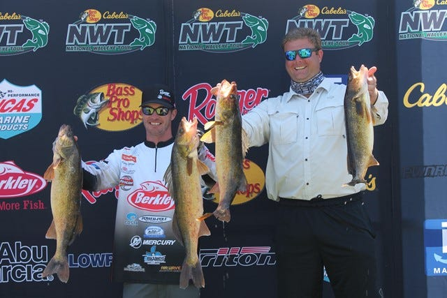Korey Sprengel of Beaver Dam, left, holds two of the fish he caught on Day 2 of the National Walley Tour event on Green Bay at Oconto on July 23-24. Sprengel won the tournament, receiving a new Ranger boat, Mercury motor and more than $17,000 in cash. At right was Sprengel's co-angler for the day, whose name was not available.