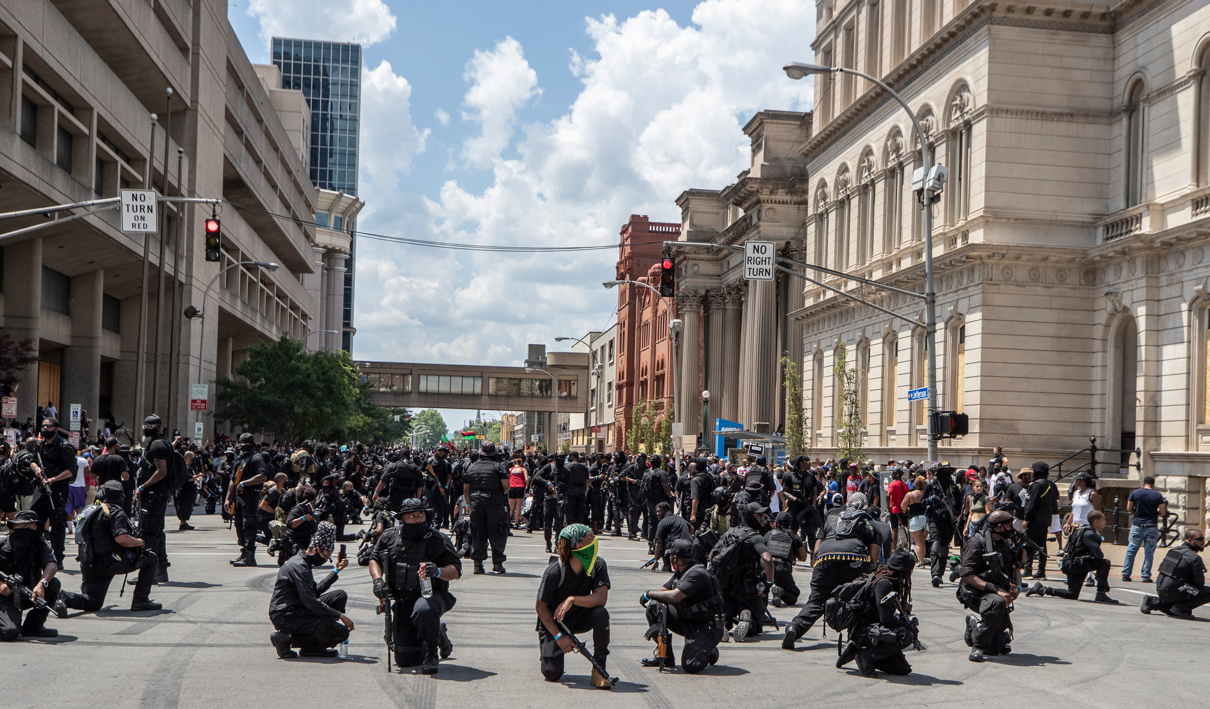 The Not F***ing Around Coalition came to Louisville in support of racial justice while the Three Percenters militia also was in town. Louisville police kept the two groups apart with barricades. The NFAC paused to check for snipers at Sixth and Jefferson streets. July 25, 2020.