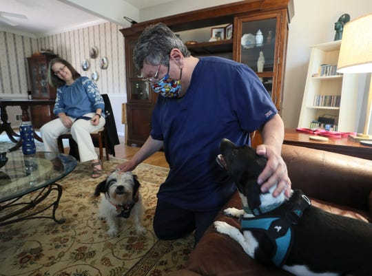 Adam Ruiz with his wife and two dogs at home on Friday, July 24, 2020.