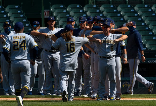 Brewers third baseman Jedd Gyorko (5) celebrates with his Brewer teammates after Saturday's victory over the Cubs.