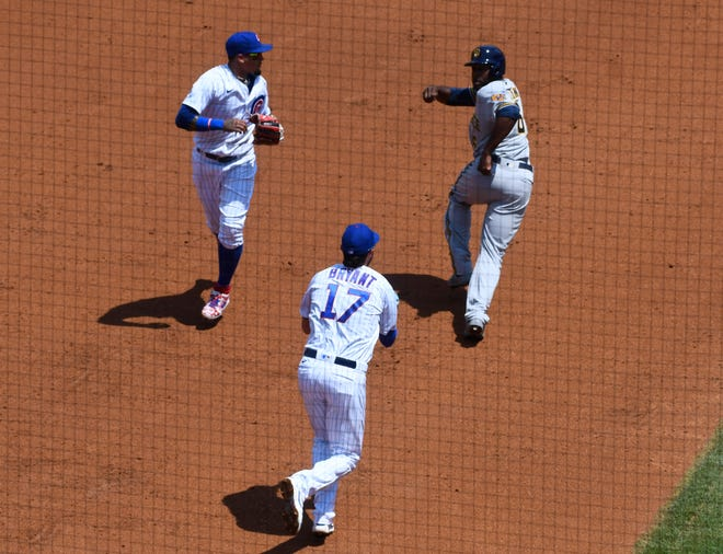 Brewers centerfielder Lorenzo Cain evades a run down with  Chicago Cubs shortstop Javier Baez  and third baseman Kris Bryant in the second inning.
