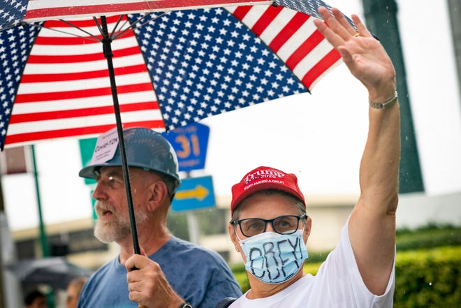 Cliff Richardson, left, and April Hoover, right, wave to passersby during a protest against the mask mandate passed by the Collier County Board of County Commissioners on Tuesday, in front of the Collier County Government Center on Friday, July 24, 2020.