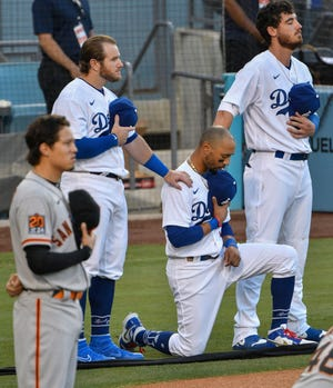 Jul 23, 2020; Los Angeles, California, USA;  Los Angeles Dodgers right fielder Mookie Betts (center) kneels during the national anthem before playing the San Francisco Giants at Dodger Stadium. Teammates Max Muncy (left) and Cody Bellinger (right) put their hands on Betts' shoulders. Mandatory Credit: Robert Hanashiro-USA TODAY Sports