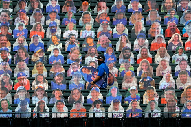 New York Mets employees place cutouts of fans in the seats before the opening day baseball game between the Mets and the Atlanta Braves at Citi Field, Friday, July 24, 2020, in New York. (AP Photo/Seth Wenig)