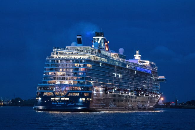 Passengers stand on board the Tui cruise ship 'Mein Schiff 2' during the departure from the port for a three-day trip on the North Sea in Hamburg, Germany, Friday, July 24, 2020. The cruise ship has set sail for the first time since the industry was shut down due to the coronavirus pandemic, with strict precautions to keep passengers and crew as safe as possible. Passengers will spend the weekend at sea with no land stops before returning to Germany on Monday.