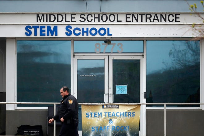 In this May 8, 2019 file photo, a Douglas County, Colo., Sheriff's deputy walks past the doors of the STEM Highlands Ranch school in Highlands Ranch, Colo.