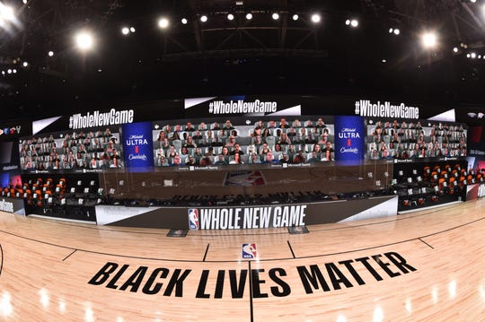 Virtual fans appear on the screen overlooking a court with a Black Lives Matter logo.