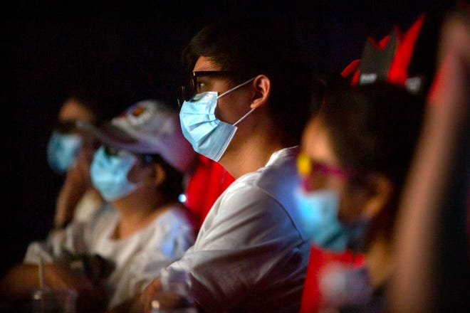 """People wearing face masks to protect against the coronavirus watch the film """"Dolittle"""" at a movie theater in Beijing, Friday, July 24, 2020. Cinemas reopened in China's capital on Friday for the first time since being closed in January due to the COVID-19 epidemic."""