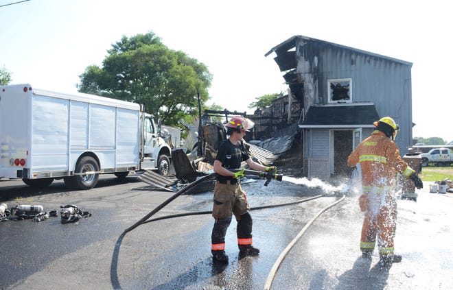 Springfield firefighters rinse each other of  debris Sunday after fire destroyed Signs and Designs in Springfield.  Trace Christenson/The Enquirer