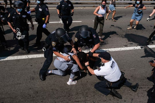 File-Black Lives Matter protesters are arrested by NYPD officers on the Brooklyn Bridge, Wednesday, July 15, 2020,