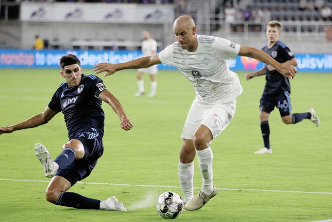 Louisville City FC's Luke Spencer (9) fights pressure from Sporting KC II's Peter Cuic (39) during the first half of play at Lynn Family Stadium in Louisville, Kentucky.     July 25,  2020.