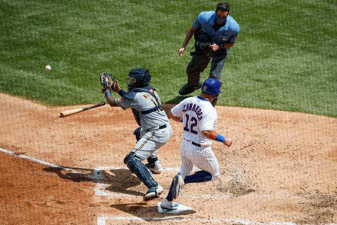 Cubs leftfielder Kyle Schwarber scores on a double by catcher Willson Contreras as Brewers catcher Omar Narvaez waits for the ball during the fourth inning at Wrigley Field on Sunday.