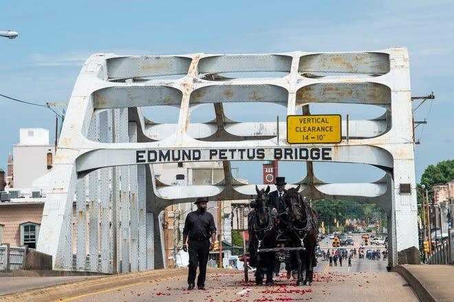 The casket of civil rights icon and U.S. Congressman John Lewis rides over the Edmund Pettus Bridge in Selma, Ala., on Saturday, July 26, 2020.