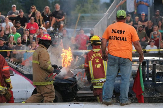 Firefighters work to put out some flames at the Ottawa County Fair's annual demolition derby, organized by the local Twisted Metal Demo Crew, on Friday.