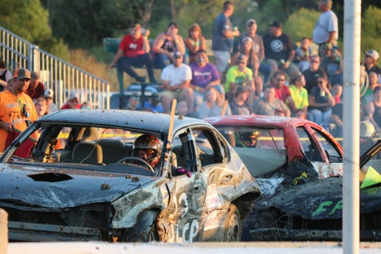 Austin Buhrow, seen here driving the red and white car to the right, looks back at the only other remaining driver, Jessica Prichard, during the final moments of the windshield heat at the Ottawa County Fair's demolition derby on Friday.