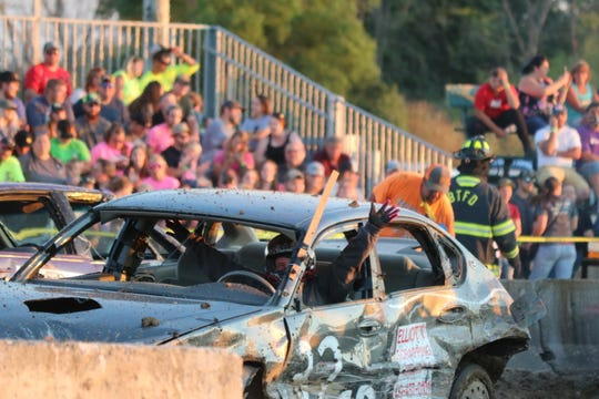 Jessica Prichard raises her hands in victory after winning the windshield heat at the Ottawa County Fair's annual demolition derby on Friday.