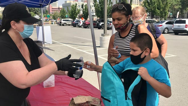 Xavier Rodriguez, 10, picks up supplies with family friend Adonica Amador, 38, and grandmother Jerri Convers, 62, from volunteers at the second annual Christmas in July event, held by the Washoe County Sheriff's Office on Saturday, July 25, 2020.