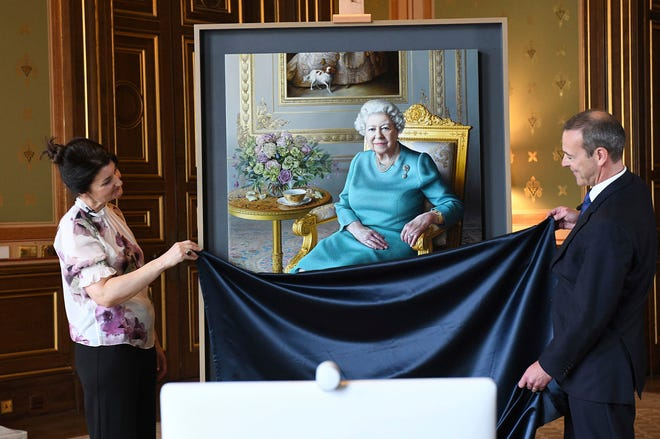 Artist Miriam Escofet, left, and Simon McDonald, Permanent Under-Secretary of State for Foreign and Commonwealth Affairs and Head of the Diplomatic Service, right, unveiled a new portrait of Britain's Queen Elizabeth II in a photo released July 25.