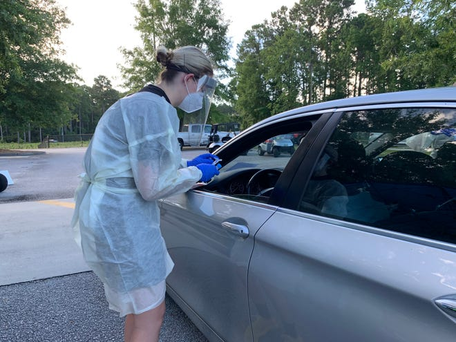 A health care professional conducts a coronavirus test during a drive-thru testing event July 22 at Bluffton High School.
