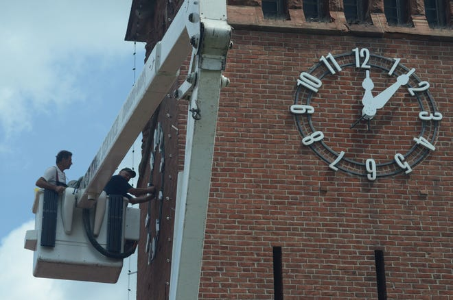 Bob Castorr, left, of C&D Tree Service of Battle Creek, and Larry Dillon of Verdin Clock Co. of Cincinnati, Ohio place new hands on the clock tower at Clara's on the River.   Trace Christenson/The Enquirer