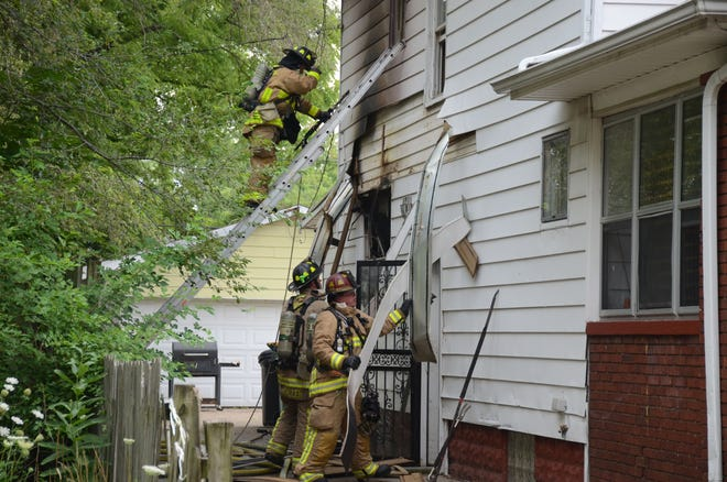 Battle Creek firefighters search for more fire at the Greenwood Avenue home.  Trace Christenson/The Enquirer