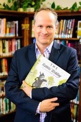 """Playwright Kenneth Jones with the book that got a school librarian in trouble in """"Alabama Story,"""" at Groves High School Jul. 30-Aug. 1."""