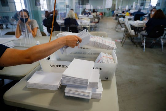 A worker gathers a bundle of ballots as they are processed at a Board of Elections facility, Wednesday, July 22, 2020, in New York. (AP Photo/John Minchillo)