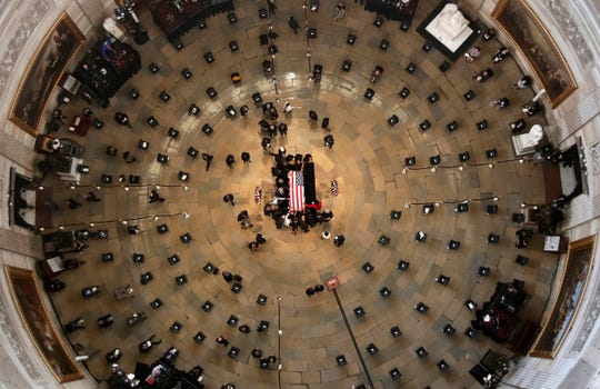 Members of the Congressional Black Caucus reach in to touch the flag-draped casket of civil rights pioneer Rep. John Lewis, D-Ga., who died July 17, in the Capitol Rotunda in Washington, Monday, July 27, 2020.