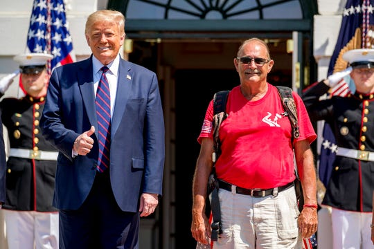 """President Donald Trump gives a thumbs up as he poses for photographs with Terry Sharpe, right, known as the """"Walking Marine"""" on Monday, July 27, 2020."""