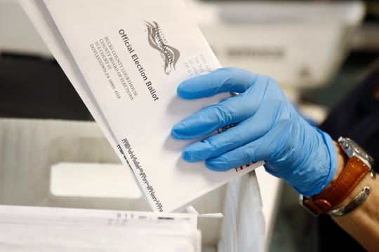 A worker processes mail-in ballots at the Bucks County Board of Elections office prior to the primary election in Doylestown, Pa.  on May 27, 2020.